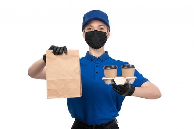 Молодая женщина-курьер в синей униформе черной маске и перчатках, держащая кофейные чашки и пакет, вид спереди