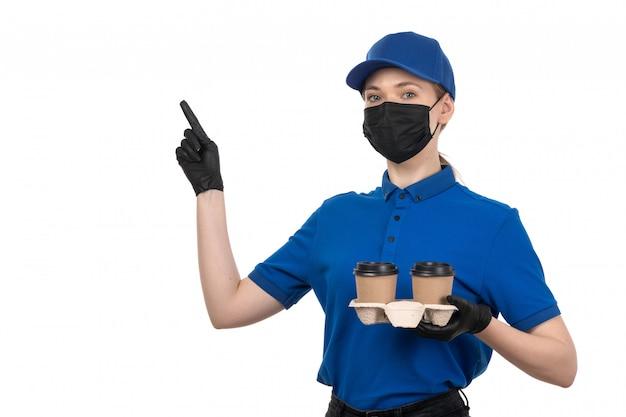 Молодая женщина-курьер в синей форме, черной маске и перчатках, держащая кофейные чашки, вид спереди