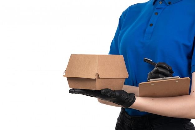 Молодая женщина-курьер в синей униформе, черной маске и перчатках, держит пакет для доставки еды и блокнот, вид спереди
