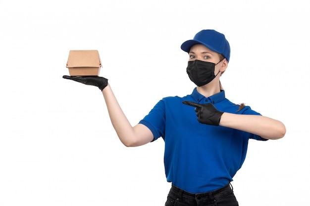 Молодая женщина-курьер в синей форме, черной маске и перчатках, держащая пакет для доставки еды, вид спереди