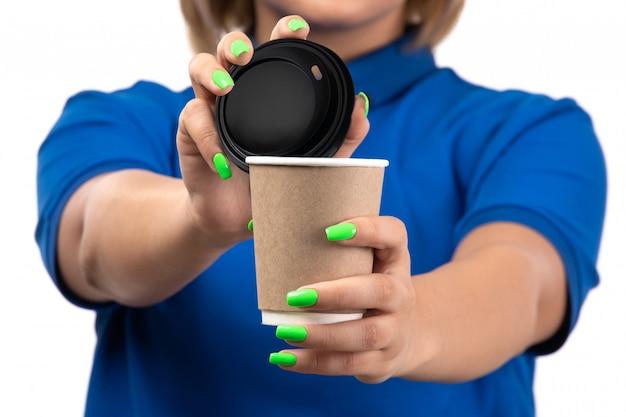 Молодая женщина-курьер в синей форме, держащая чашку кофе, вид спереди