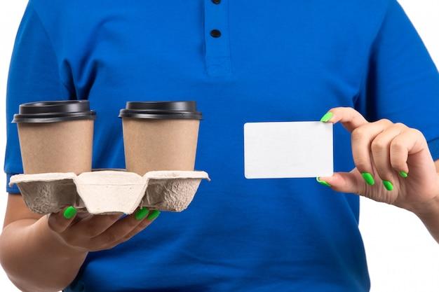 Молодая женщина-курьер в синей форме, держащая кофейные чашки и белую карточку, вид спереди