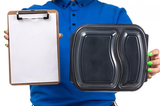 Молодая женщина-курьер в синей форме, держащая миску для доставки еды и блокнот для подписей, вид спереди