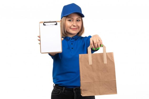 Молодая женщина-курьер в синей форме, держащая пакет для доставки еды и блокнот для подписей, вид спереди
