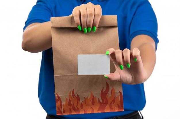 Молодая женщина-курьер в синей форме, держащая пакет для доставки еды и белую карточку, вид спереди
