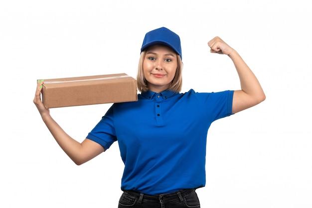 Молодая женщина-курьер в синей форме, держащая пакет для доставки еды с улыбкой на лице, вид спереди