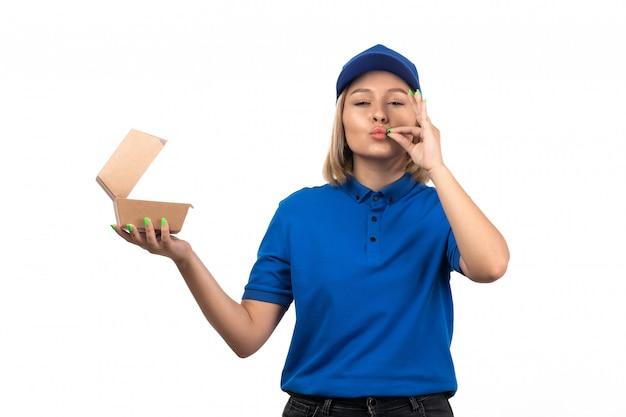 Молодая женщина-курьер в синей форме, держащая пакет для доставки еды, вид спереди