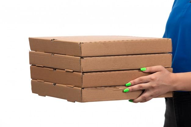Молодая женщина-курьер в синей форме с улыбкой держит пакеты для доставки еды