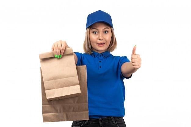 Молодая женщина-курьер в синей форме, держащая пакеты с доставкой еды, вид спереди