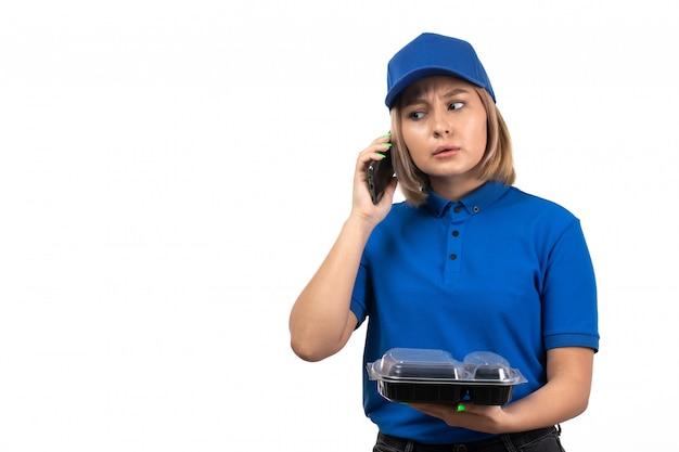 Молодая женщина-курьер в синей форме, держащая телефон и миску с едой, вид спереди
