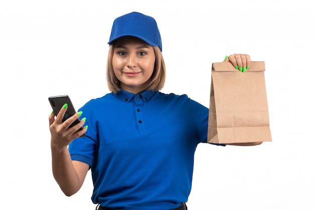 Молодая женщина-курьер в синей форме, держащая телефон и пакет для доставки еды, вид спереди