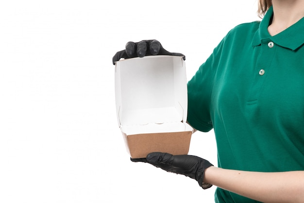 Молодая женщина-курьер в зеленой форме, черные перчатки и черная маска, держащая пустой пакет для доставки еды, вид спереди