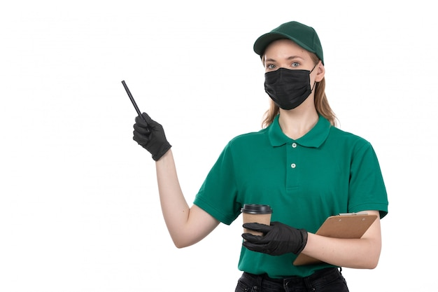 緑の均一な黒い手袋とコーヒーカップとメモ帳を保持している黒いマスクの正面の若い女性の宅配便