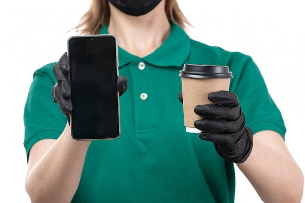 緑の均一な黒い手袋とコーヒーカップと電話を保持している黒いマスクの正面の若い女性の宅配便