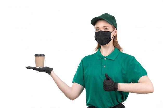 Молодая женщина-курьер в зеленой униформе, черные перчатки и черная маска, держащая чашку кофе, вид спереди