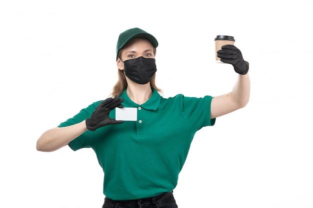 緑の均一な黒い手袋とコーヒーカップを保持している黒いマスクの正面の若い女性の宅配便