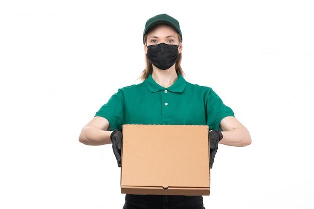 Вид спереди молодая женщина-курьер в зеленой форме, черные перчатки и черная маска, держащая доставку посылки с доставкой