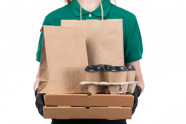 Вид спереди молодая женщина-курьер в зеленой форме, черные перчатки и черная маска, держащая доставку пакетов с доставкой еды