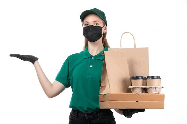 緑の制服の黒い手袋とフードデリバリーパッケージを提供する保持している黒いマスクの正面の若い女性宅配便