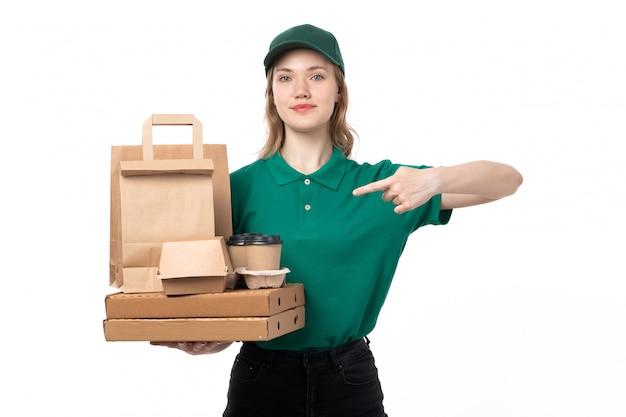 Молодая женщина-курьер в зеленой форме, держащая пакеты с кофейными чашками и улыбаясь, вид спереди