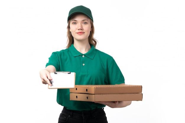 Молодая женщина-курьер в зеленой форме, держащая коробки для пиццы и блокнот, вид спереди