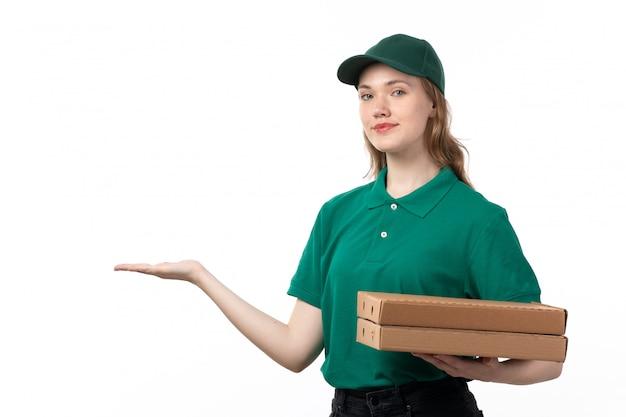 Молодая женщина-курьер в зеленой форме, держащая коробки для доставки пиццы, показывает ее пустую ладонь, вид спереди