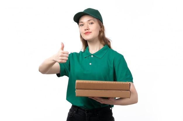 Молодая женщина-курьер в зеленой форме, держащая коробки для доставки пиццы, показывает как знак