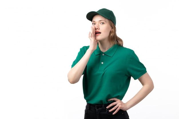 Вид спереди молодая женщина-курьер в зеленой форме позирует и шепчет