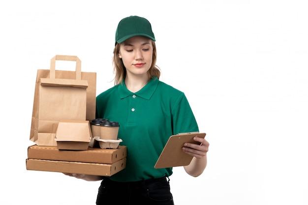 Молодая женщина-курьер в зеленой униформе, улыбаясь, держит в руках доставку еды и блокнот