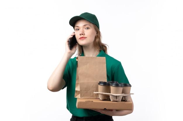 Молодая женщина-курьер в зеленой униформе, улыбаясь, держит кофейные пакеты с едой и разговаривает по телефону
