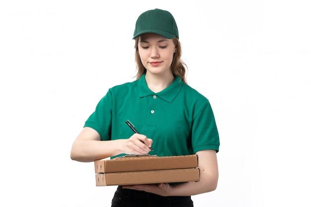 Молодая женщина-курьер в зеленой форме, улыбаясь, держит коробки с едой и блокнот для подписей, вид спереди