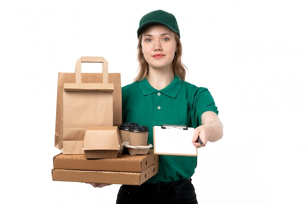 Молодая женщина-курьер в зеленой форме улыбается, держит коробки с продуктами и просит подпись