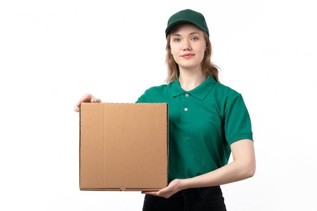 Молодая женщина-курьер в зеленой форме, улыбаясь, держит пакет с едой, вид спереди