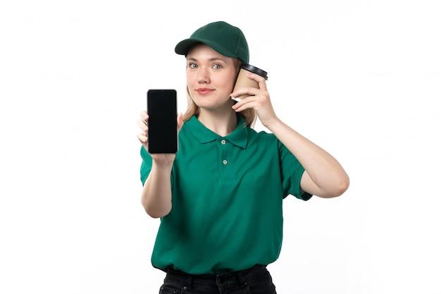 Молодая женщина-курьер в зеленой форме, улыбаясь, держит смартфон и чашку кофе, вид спереди