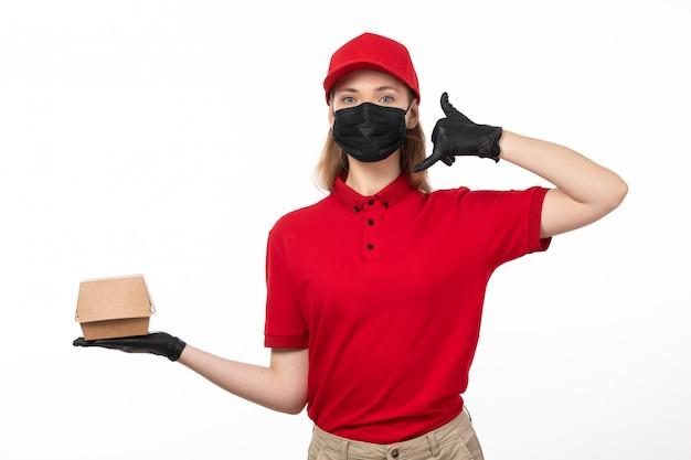 Вид спереди молодой женщины-курьера в красной рубашке, красной кепке, черных перчатках и черной маске, держащей пакет с едой