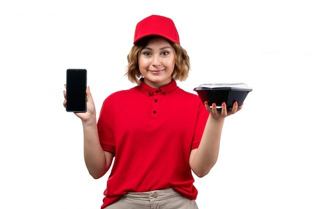 正面を向いた若い女性の宅配便赤いシャツの赤い帽子ホールディングボウルに電話を笑顔の食品