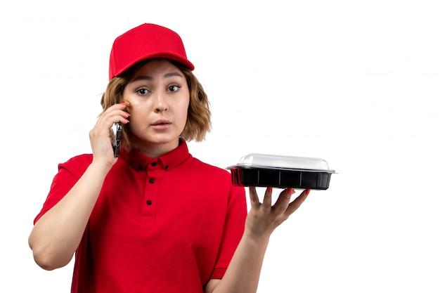 電話で話している食物と一緒にボウルを保持している赤いシャツの赤い帽子の正面の若い女性の宅配便