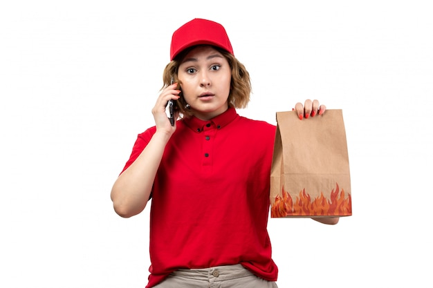 Молодая женщина-курьер в красной рубашке с красной кепкой, держащая пакет с доставкой еды, разговаривает по телефону