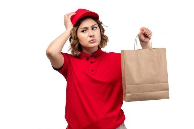 Вид спереди молодая женщина-курьер в красной рубашке с красной кепкой, держащая пакет доставки на белом фоне, доставка униформы