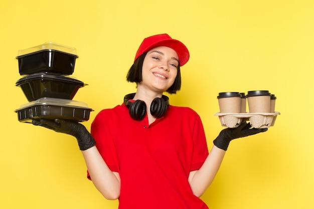 Вид спереди молодой женщины курьер в красных форменных черных перчатках и красной шапочке с мисками и кофейными чашками