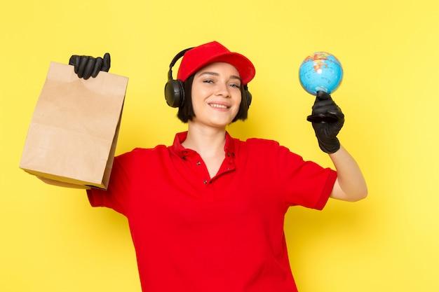 Вид спереди молодой женщины курьер в красной форме черные перчатки и красной шапочке, держа коробку с едой и маленький глобус