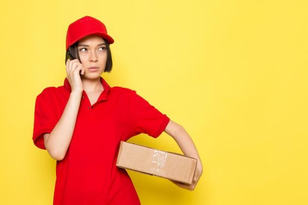 Вид спереди молодой женщины курьер в красной форме черные перчатки и красной кепке держит коробку с едой и разговаривает по телефону