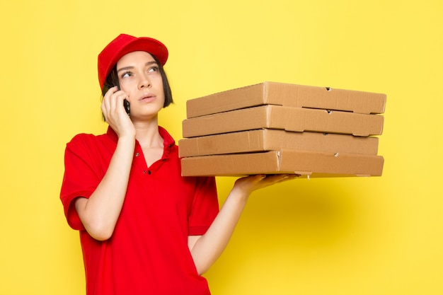 Вид спереди молодой женщины курьер в красной форме черные перчатки и красной кепке держит коробки с едой и разговаривает по телефону