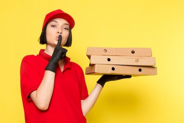 赤い制服の黒い手袋とフードボックスを保持している赤い帽子の正面の若い女性の宅配便