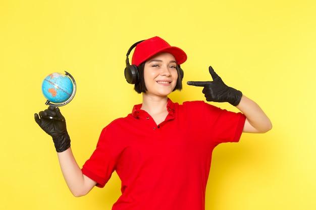 Вид спереди молодой женщины курьер в красной форме черные перчатки и красной кепке, держа маленький глобус, слушая музыку