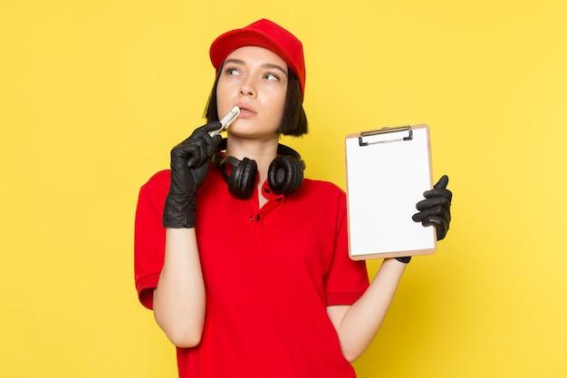 赤い制服の黒い手袋と思考の表現でペンとメモ帳を保持している赤い帽子の正面の若い女性宅配便