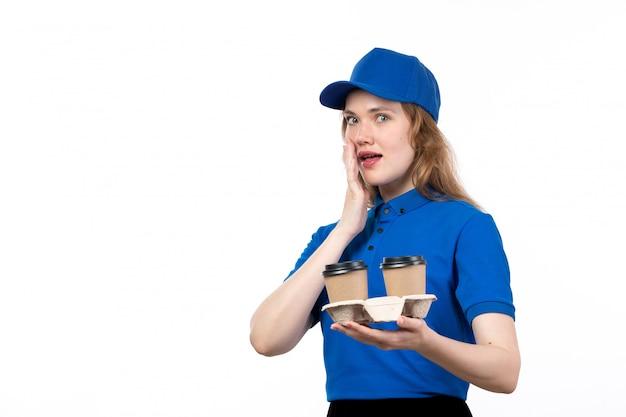 Молодая женщина-курьер в форме, держащая чашки с застенчивым выражением лица кофе, вид спереди