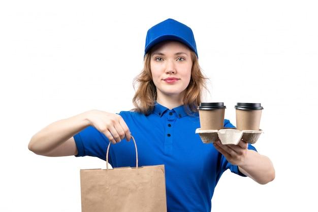 笑顔のコーヒーカップと配信パッケージを保持している制服を着た正面若い女性宅配便