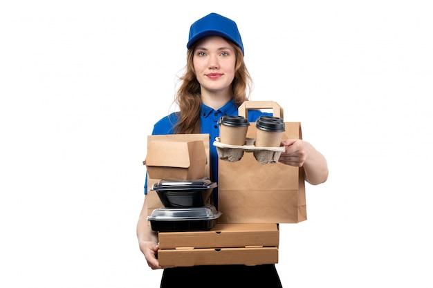 配信パッケージボックスとコーヒーの笑顔を保持している制服を着た正面の若い女性宅配便