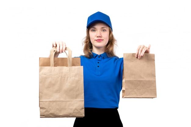笑顔の配信パッケージを保持している制服を着た正面の若い女性宅配便